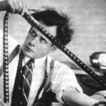 portrait d'Eisenstein en noir et blanc regardant les vignettes d'une pellicule de cinéma.